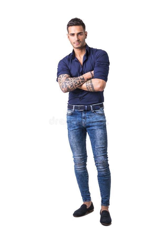 蓝色被隔绝的衬衣和牛仔裤的年轻人 免版税库存图片