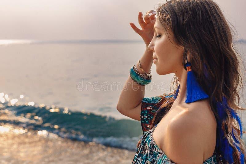 蓝色裙子的美丽的年轻时髦的妇女在海滩 免版税库存照片