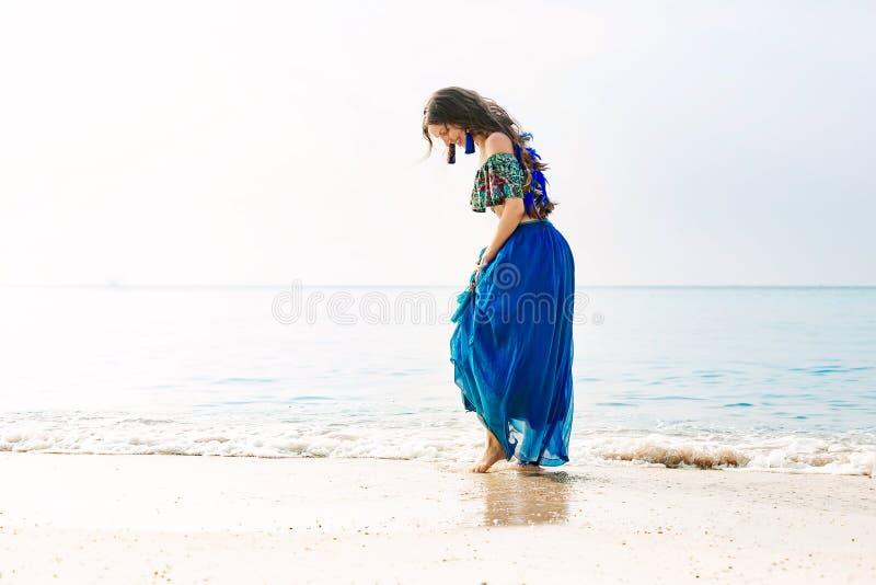 蓝色裙子的美丽的年轻时髦的妇女在海滩 库存图片