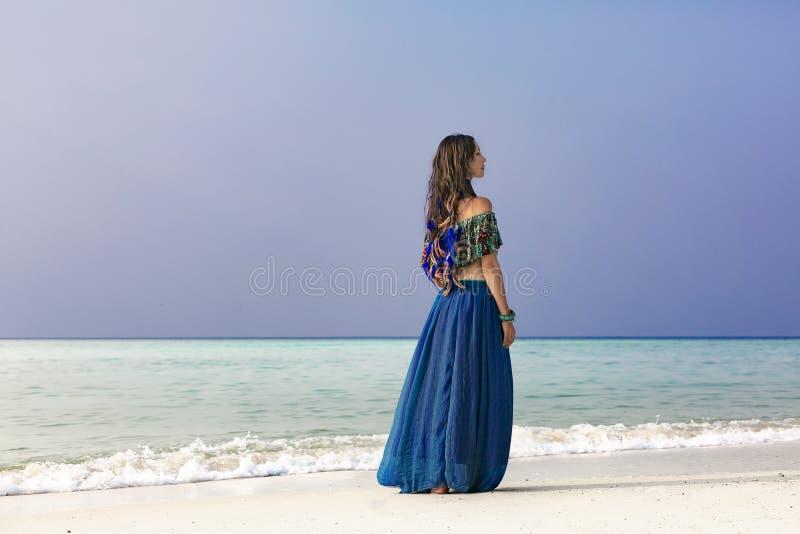 蓝色裙子的美丽的年轻时髦的妇女在海滩 图库摄影