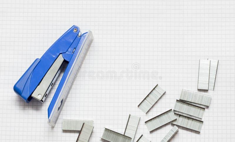蓝色订书机和堆在纸的办公室钉书针, Clos 免版税库存照片
