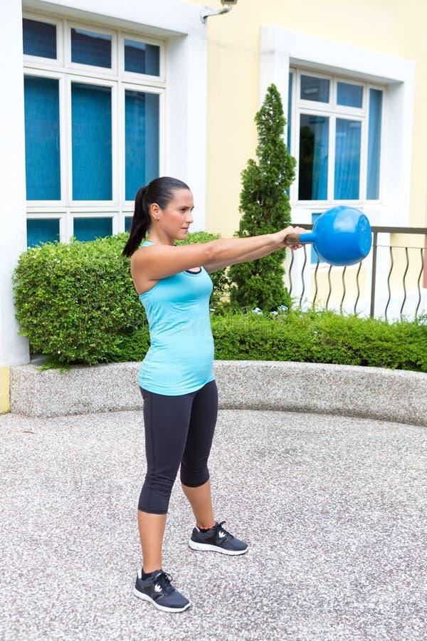 蓝色训练的运动的西班牙妇女与显示摇摆惯例的kettlebell 库存照片