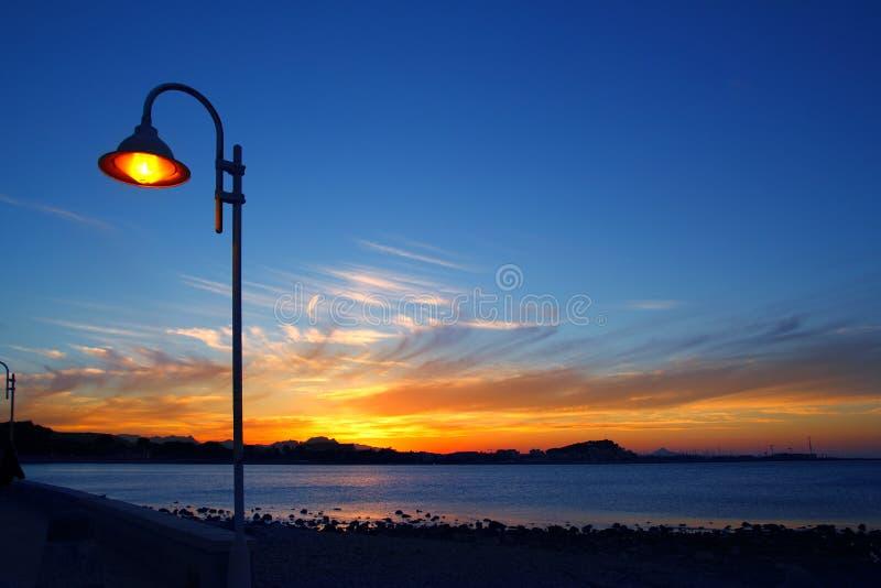 蓝色路灯柱淡桔色的海景日落 图库摄影