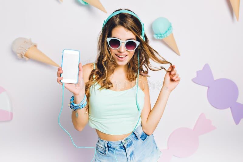 蓝色辅助部件听的音乐的高兴的女孩在她的屋子里,拿着智能手机和使用与头发 画象典雅 免版税库存图片