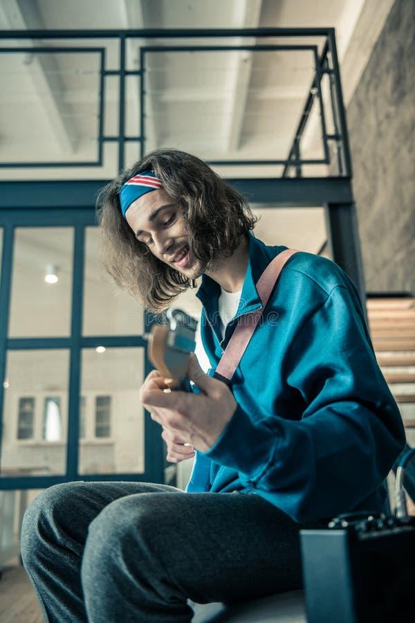 蓝色运动衫运载的吉他的满足的深色头发的被启发的人 免版税库存照片