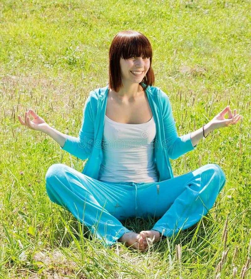 蓝色适合的女孩实践的瑜伽 免版税库存图片