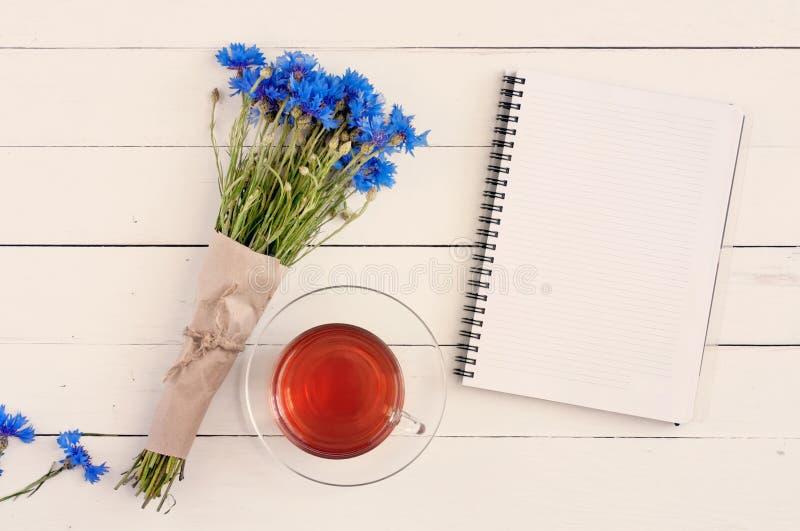 蓝色野花美丽的花束与一本空的便笺的为 免版税库存图片