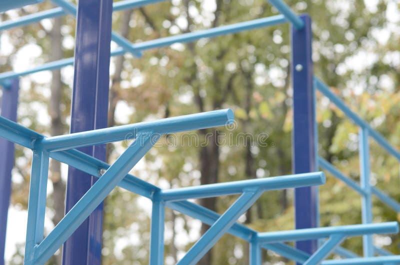 蓝色金属管子和标志横线反对一个街道运动场训练的在竞技方面 室外运动健身房设备 宏指令 免版税库存图片