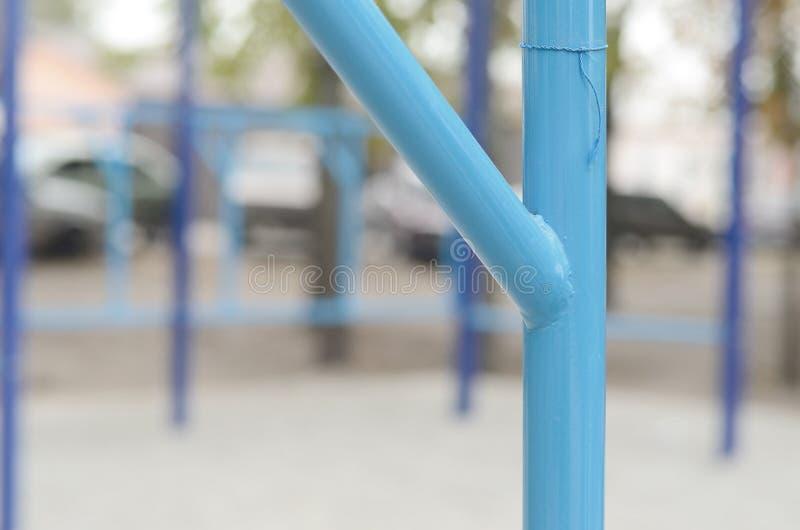 蓝色金属管子和标志横线反对一个街道运动场训练的在竞技方面 室外运动健身房设备 宏指令 库存图片
