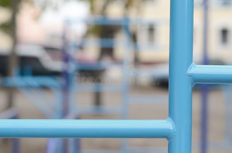蓝色金属管子和标志横线反对一个街道运动场训练的在竞技方面 室外运动健身房设备 宏指令 免版税库存照片