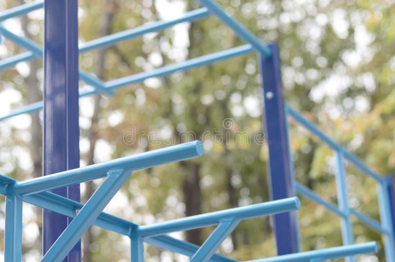 蓝色金属管子和标志横线反对一个街道运动场训练的在竞技方面 室外运动健身房设备 宏指令 库存照片