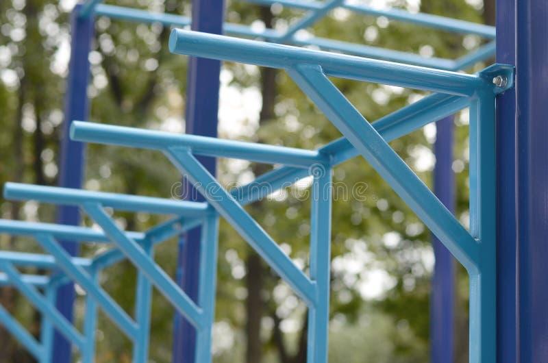 蓝色金属管子和标志横线反对一个街道运动场训练的在竞技方面 室外运动健身房设备 宏指令 免版税图库摄影