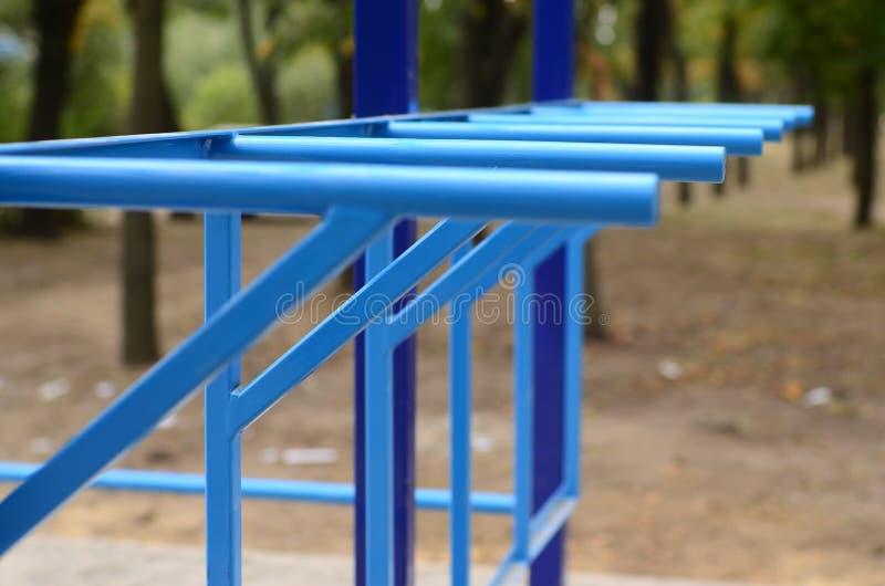 蓝色金属管子和标志横线反对一个街道运动场训练的在竞技方面 室外运动健身房设备 宏指令酸碱度 库存照片