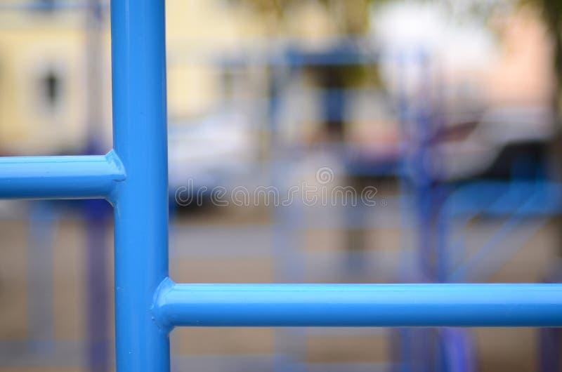 蓝色金属管子和标志横线反对一个街道运动场训练的在竞技方面 室外运动健身房设备 宏指令酸碱度 库存图片