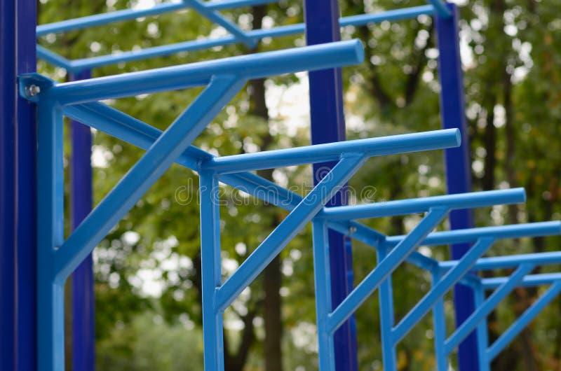 蓝色金属管子和标志横线反对一个街道运动场训练的在竞技方面 室外运动健身房设备 宏指令酸碱度 免版税库存照片