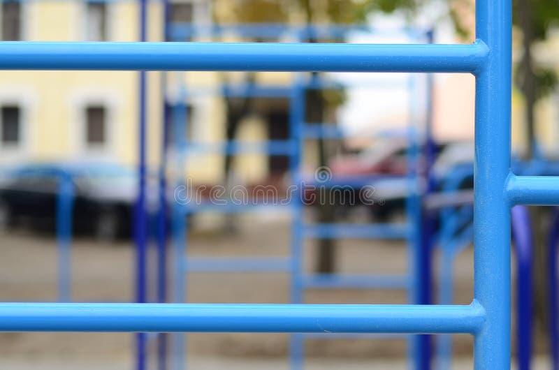 蓝色金属管子和标志横线反对一个街道运动场训练的在竞技方面 室外运动健身房设备 宏指令酸碱度 图库摄影