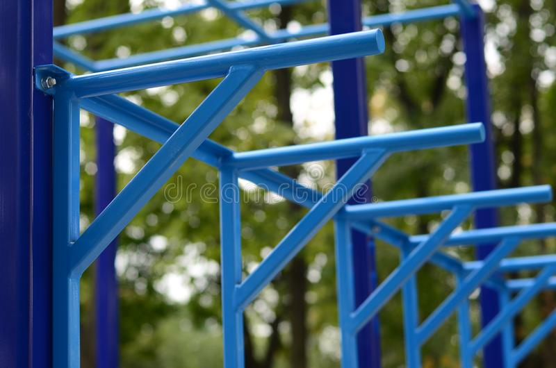 蓝色金属管子和标志横线反对一个街道运动场训练的在竞技方面 室外运动健身房设备 宏指令酸碱度 免版税库存图片