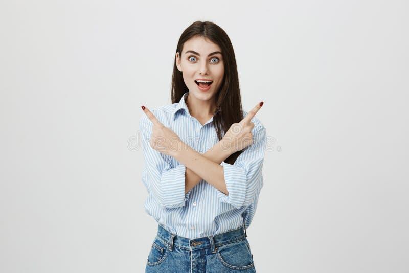 蓝色镶边衬衣和牛仔裤的吃惊的和激动的年轻白种人学生指向斜向一边用横渡的手的和 图库摄影
