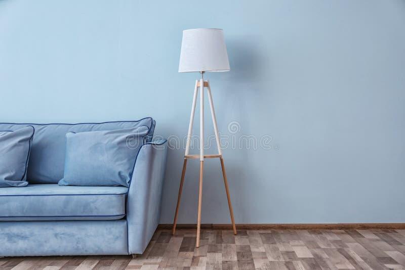 蓝色长沙发和落地灯在墙壁附近 库存图片