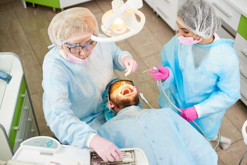 蓝色长袍的两位女性牙医参加牙科的一个男性客户的牙 免版税库存图片