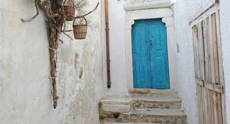 蓝色门对白色墙壁 库存图片