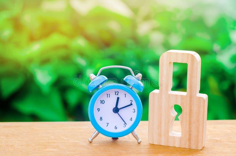 蓝色闹钟和挂锁 警报或一个临时禁令的概念,结冰 非耐久性的保护经过时间检验的保护 免版税库存图片