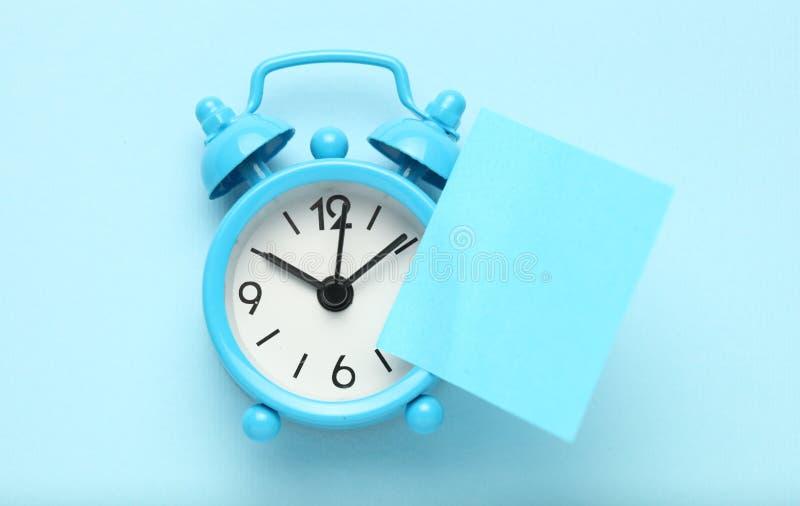 蓝色闹钟和提示笔记 E r 库存照片