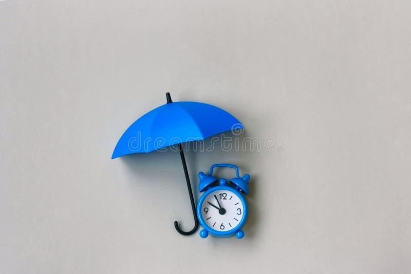 蓝色闹钟在伞下 库存照片