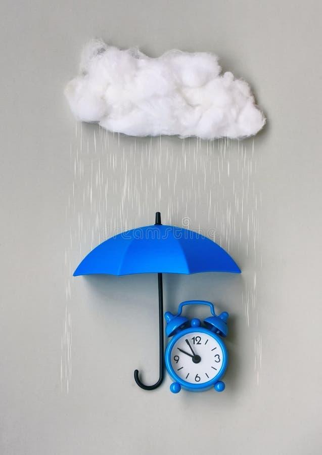 蓝色闹钟在灰色背景的一把伞下 库存照片