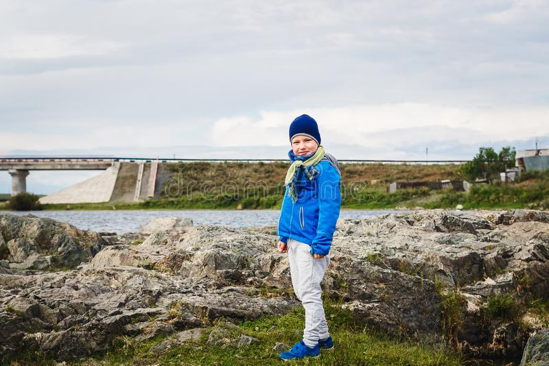 蓝色防风上衣立场的微笑的男孩在河附近的石头在春天 免版税库存照片