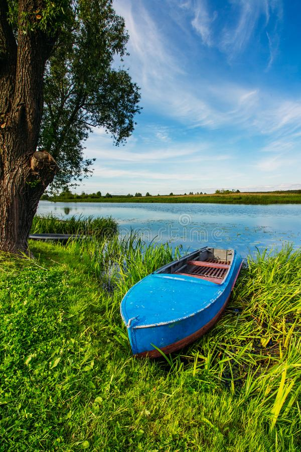 蓝色颜色渔船在河岸的 库存照片