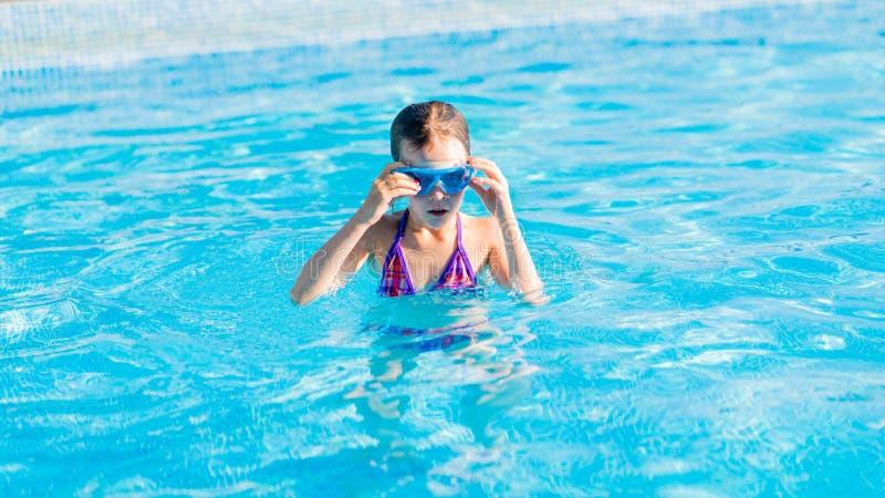 蓝色风镜的愉快的女孩游泳在游泳池的 免版税图库摄影