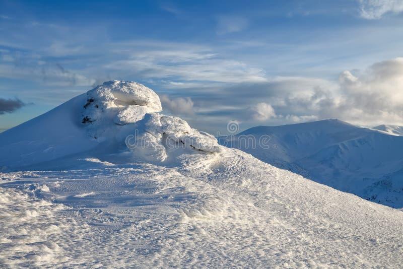 蓝色高山山脉天空冬天 神奇意想不到的岩石结冰与奇怪的童话形式和结构冰和雪  免版税库存照片