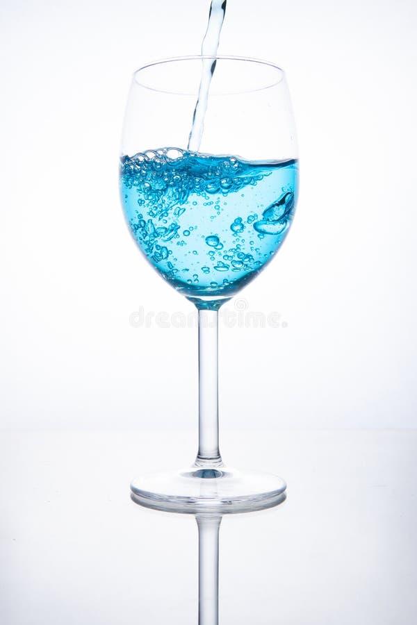 蓝色鸡尾酒涌入在白色背景的一块玻璃与反射,飞溅并且起泡 库存照片