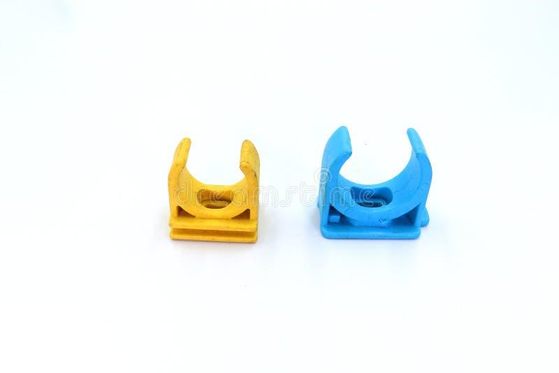 蓝色,黄色PVC管接头和在白色背景隔绝的管子夹子 库存图片