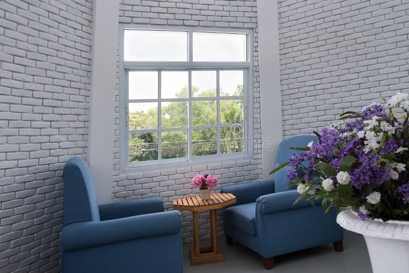 蓝色经典扶手椅子在有白色bric的现代顶楼客厅 免版税库存照片