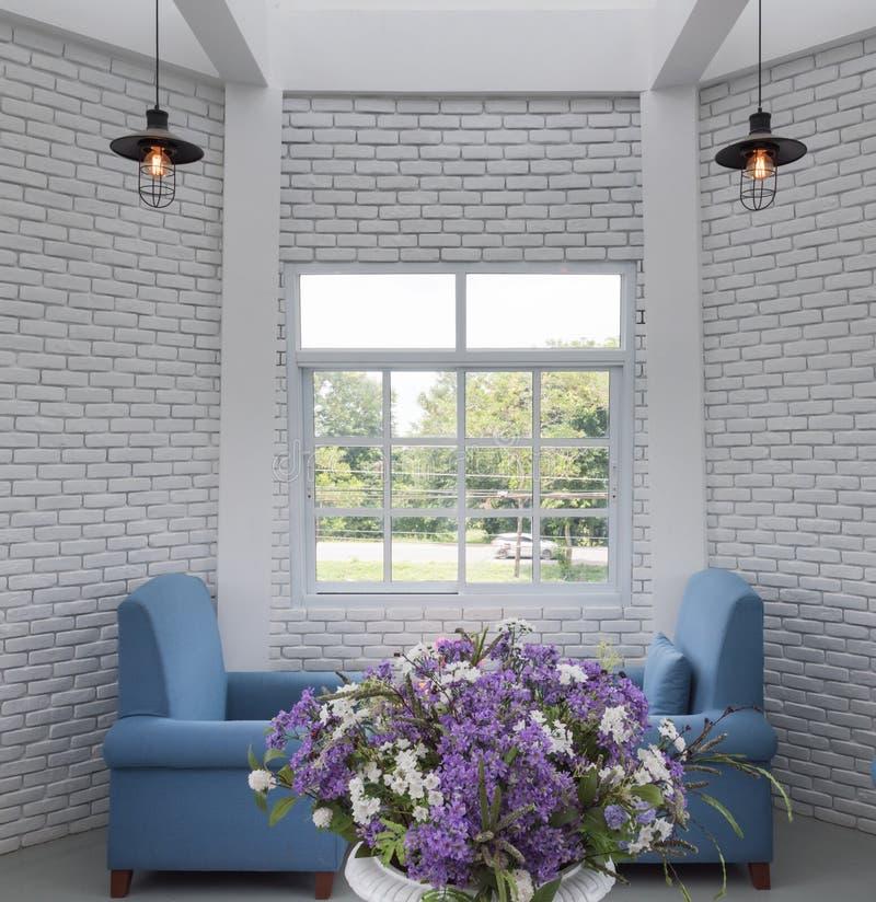 蓝色经典扶手椅子在有白色bric的现代顶楼客厅 库存图片