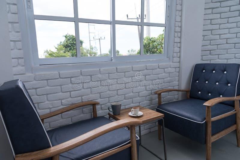 蓝色经典扶手椅子在有白色bric的现代顶楼客厅 免版税库存图片