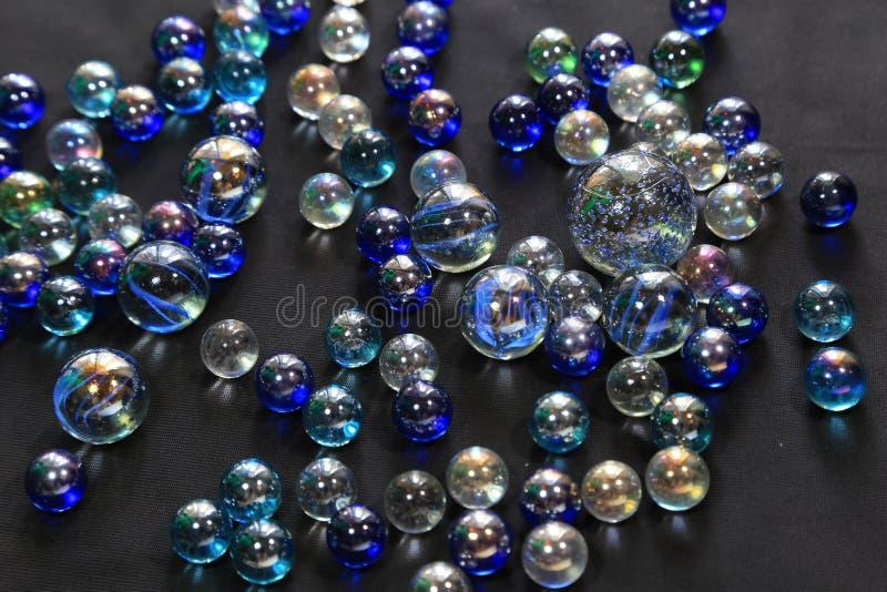 蓝色玻璃珠的各种各样的颜色和大小在黑背景的 库存照片