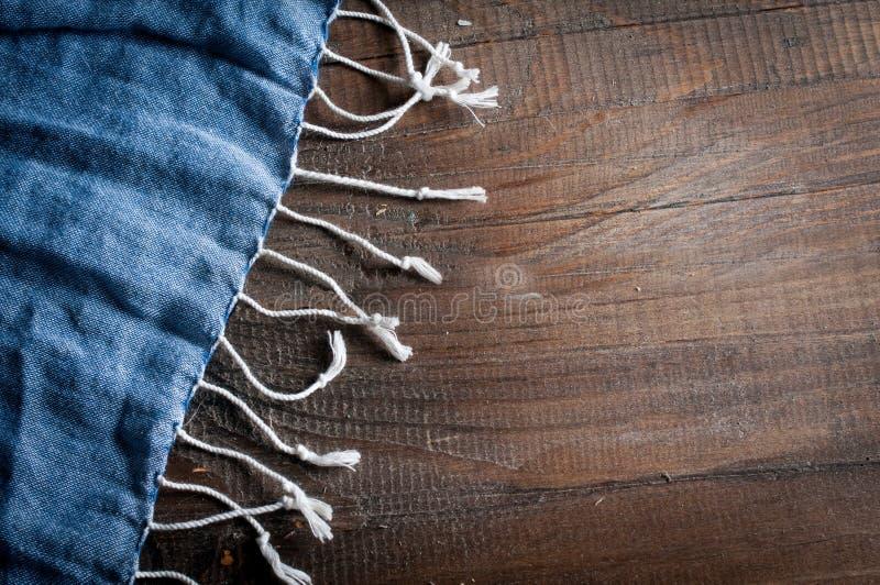 蓝色轻的妇女围巾细节在一个黑暗的木纹理特写镜头的 库存图片