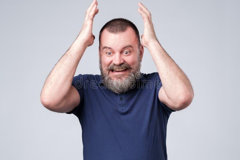 蓝色T恤杉传神姿势示意的成熟人用手,设法证明他的看法 库存图片