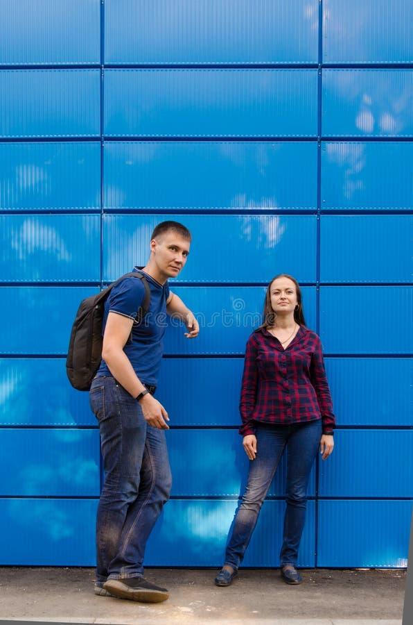蓝色T恤杉和背包的人在他在蓝色牛仔裤和格子衬衫打扮的女孩旁边对蓝色墙壁 r 免版税库存照片
