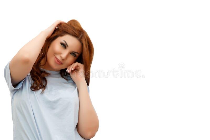 蓝色T恤杉的年轻美丽的红头发人妇女在白色被隔绝的背景 免版税库存照片