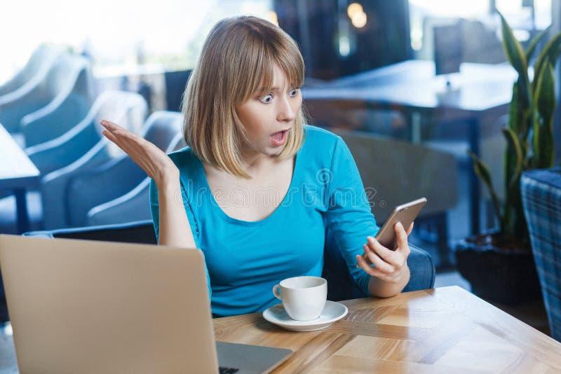 蓝色T恤杉的,坐在咖啡馆和举行她流动智能手机和看的年轻震惊白肤金发的妇女顶视图画象 免版税库存照片