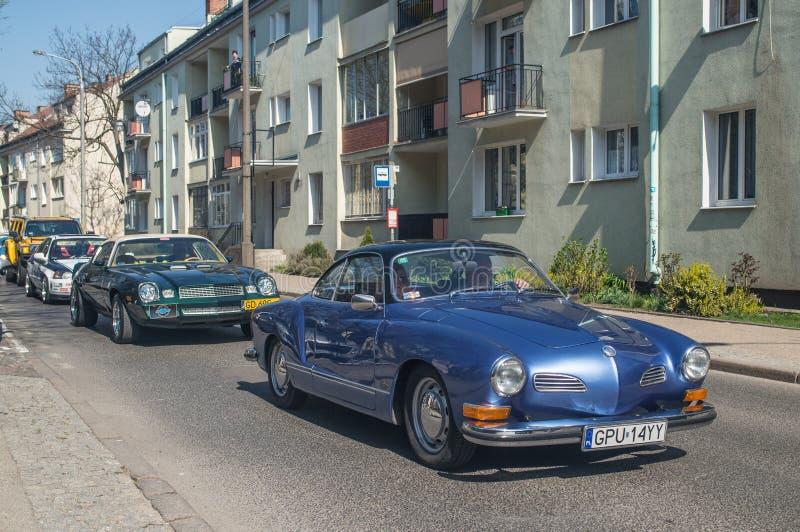 蓝色VW Karmann驾驶与老汽车的吉阿 库存照片