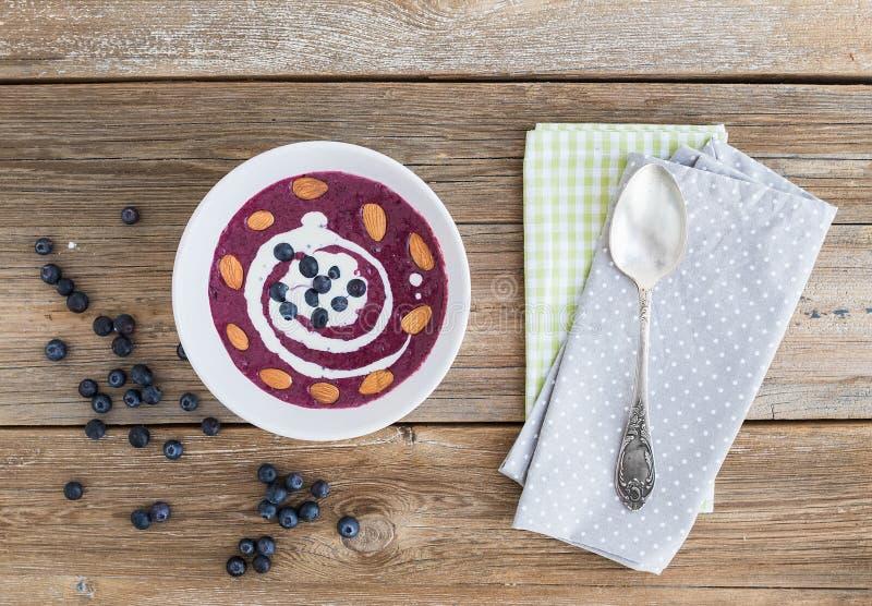 蓝莓和奶油汤用在概略的木表面的杏仁 免版税库存图片