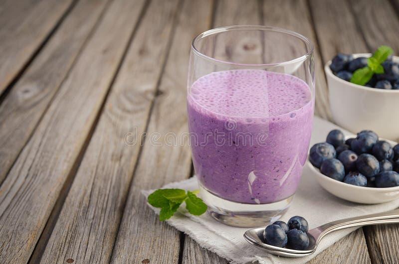 蓝莓和香蕉圆滑的人用在土气木桌上的燕麦粥 库存照片