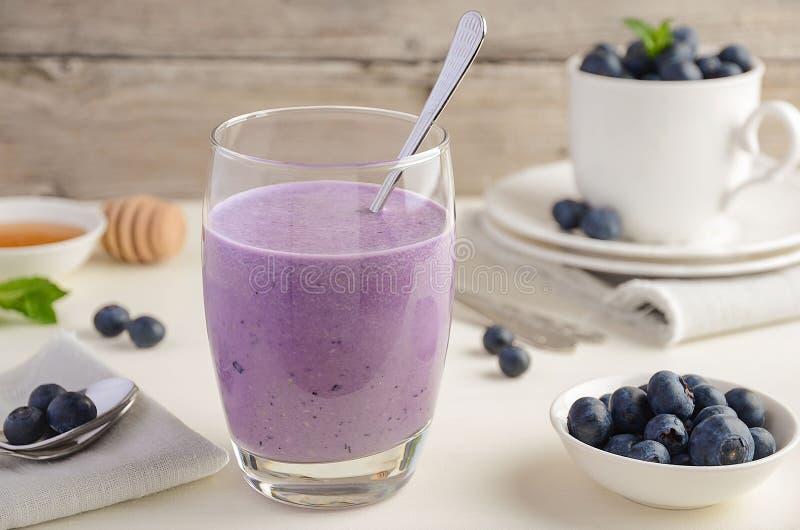 蓝莓和香蕉圆滑的人用在土气木桌上的燕麦粥 免版税库存图片