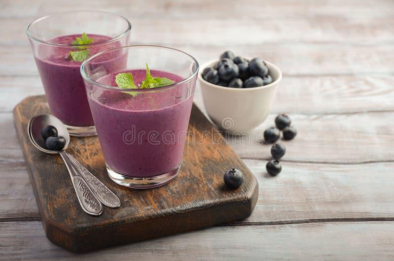蓝莓和香蕉圆滑的人用在土气木桌上的燕麦粥 库存图片