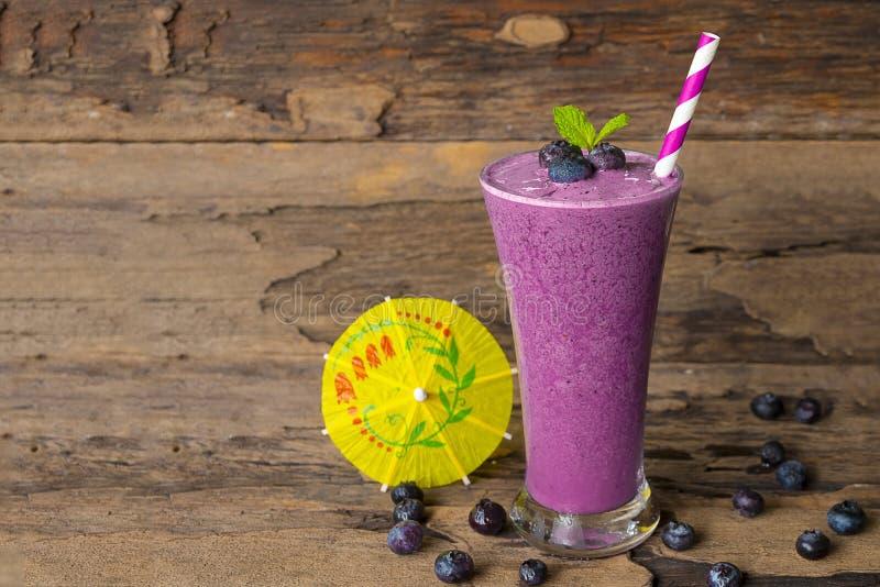 蓝莓圆滑的人汁液和蓝莓果子黑色饮料可口在一个玻璃早晨在木背景喝 库存照片